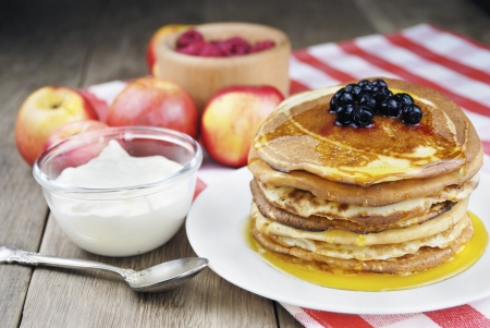 Pile of pancakes with berries in the white plate on the wooden table photo