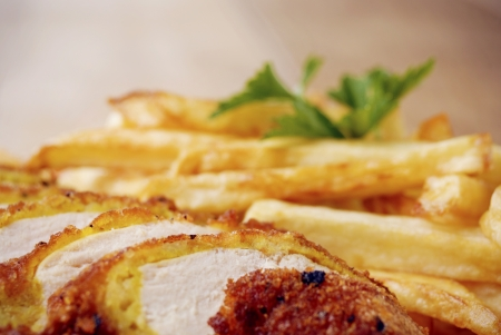 sause: Fresh tasty french fries and chicken on the plate on the wooden table along with vegetables Stock Photo