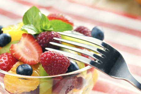 Sweet tasty fruit salad in the bowl on the wooden table photo
