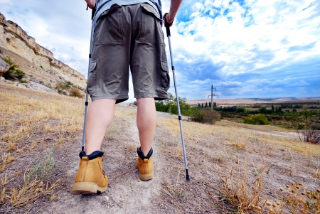 Adult man is hiking with trekking poles in the mountains photo