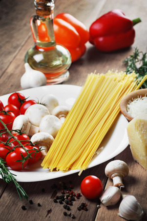 Pasta ingredients on the wooden table with vegetables and olive oil photo