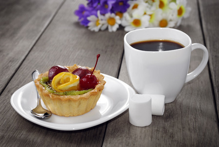 Hot coffee and tasty cake on the wooden table photo