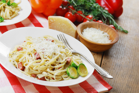 Pasta carbonara in the white plate on the wooden table photo