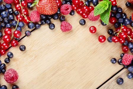 Bright summer frame of fresh sweet berries on the table photo