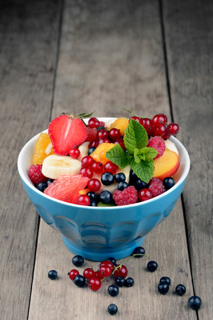 woden: Fresh tasty fruit salad in the bowl on the wooden table Stock Photo