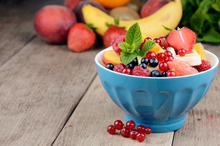 Verse smakelijke fruitsalade in de kom op de houten tafel