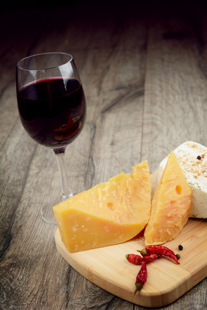 tabla de quesos: Queso en la mesa de madera con un vaso de vino