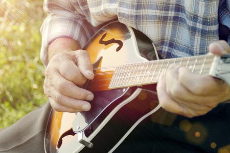mandolin: Senior man playing mandolin outside on the green background