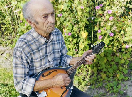 mandolino: Uomo maggiore che gioca il mandolino di fuori su sfondo verde