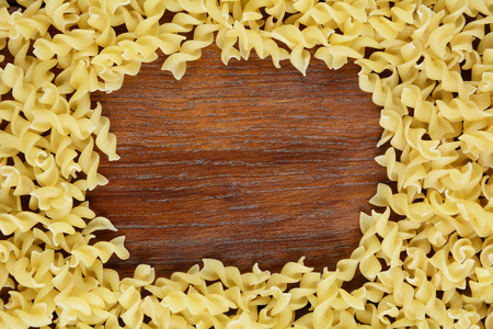 Raw fusilli pasta background on the wooden table Stock Photo