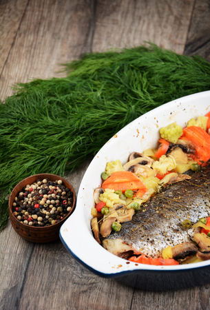 Baked saebass fish with vegetables on the table Stock Photo