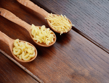 Tree wooden spoons with different kinds of pasta on the table Stock Photo