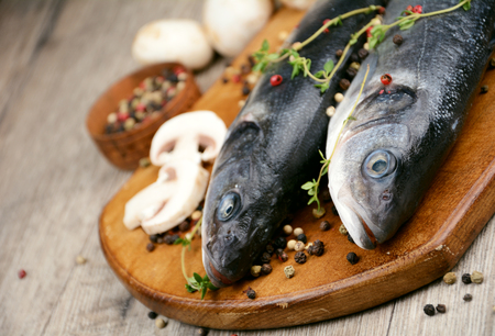Raw seabass fish on the wooden board with vegetables