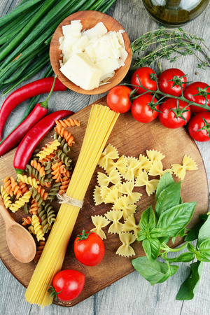 Different kinds of raw pasta on the wooden table Stock Photo