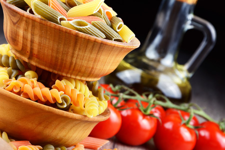 Raw eliche and penne tricolori pasta in the wooden bowls on the table
