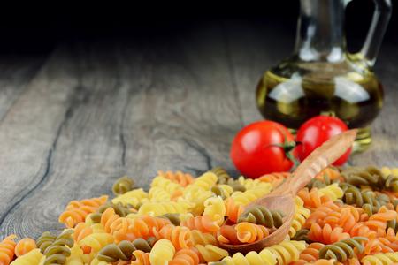 Raw eliche tricolori pasta background on the wooden table