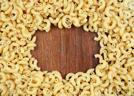Raw Chifferi pasta background on the wooden table
