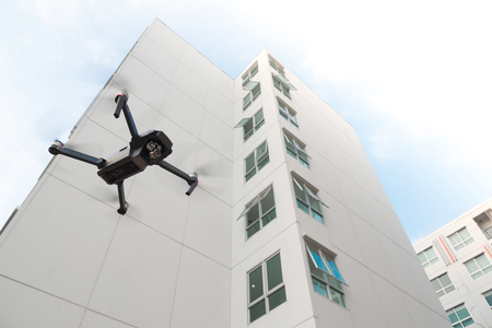 Drone with high resolution digital camera flying over on residential building background.