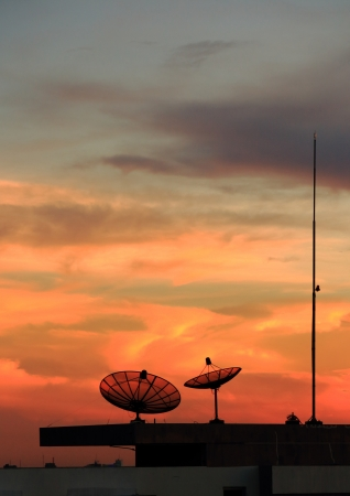 Satellite dish on the roof at sunset   photo