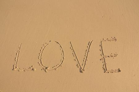 valentine s day beach: The Inscription on the Sand near the Sea - LOVE