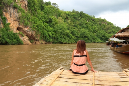 Woman Relaxing on a Bamboo Raft Floats on Kwainoi River with Wild landscape in Kanchanaburi, Thailand  photo