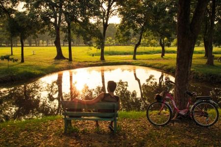 Man with Bicycle Sitting on Bence and Enjoying Sunset over Lake  photo