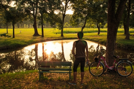 Man with Bicycle Standing on Ground and Enjoying Sunset over Lake  photo
