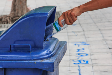 Hand throwing Bottle  in the Litter Bin. photo