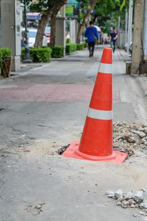 pothole: Traffic cone covering on pothole. Stock Photo