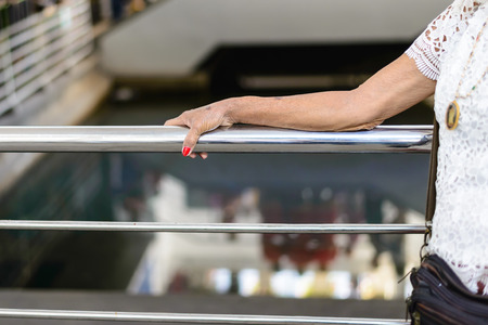 banister: Old woman hand touching a metal banister. Stock Photo