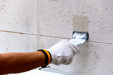 Painting white color on cement wall by paintbrush.