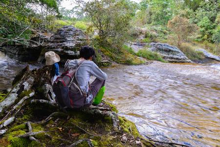 Hiker resting near waterfall. photo