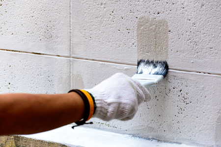 Painting white color on cement wall by paintbrush. Banco de Imagens - 34564533