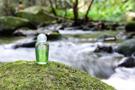 amenities: Spa shampoo on moss stone with waterfall background.