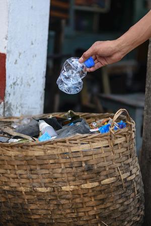 whitern: Hand throwing bottle in the basket bin.