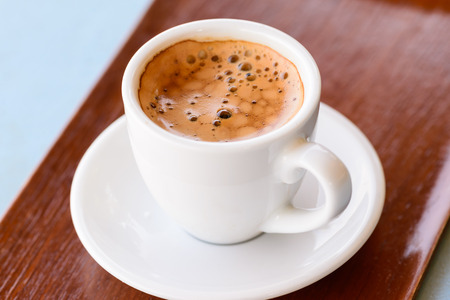 fresh morning: Hot espresso in white cup on wooden tray.