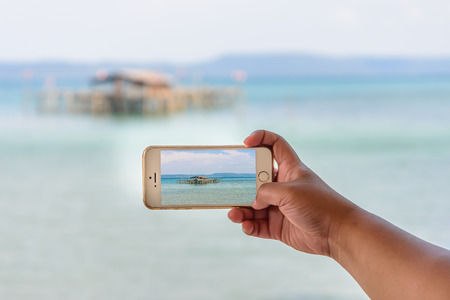 Taking photo of seascape with smartphone.
