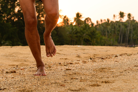 Barefoot running on beach at sunset. Stock Photo