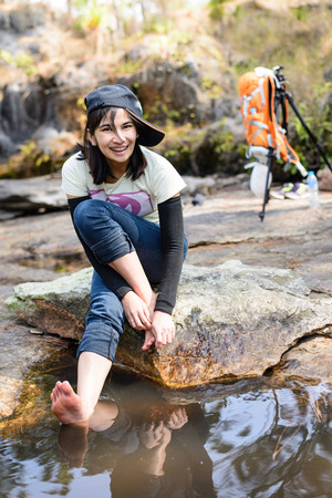 Woman hiker break in a journey using natural liquid immersion foot, which is a good way to health.