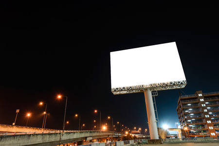 Blank billboard near expressway at night for advertisement.