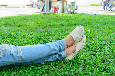 unwinding: Cropped woman legs in denim with white sneakers resting on grass.