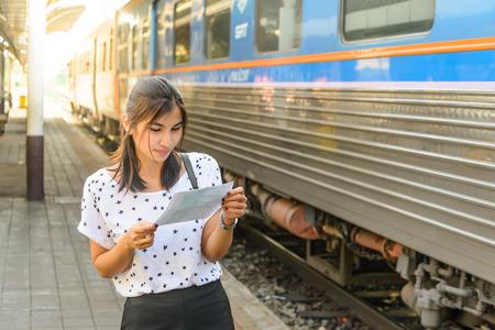 wayfarer: Woman watching a ticket before boarding the train at platform.