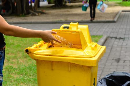reciclar: La mano que lanza botella en la arena amarilla Bin. Foto de archivo