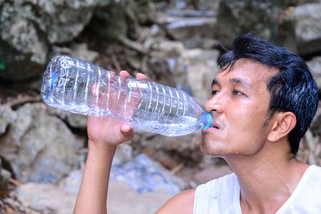 roasting: Man hiker drinking water in roasting day.