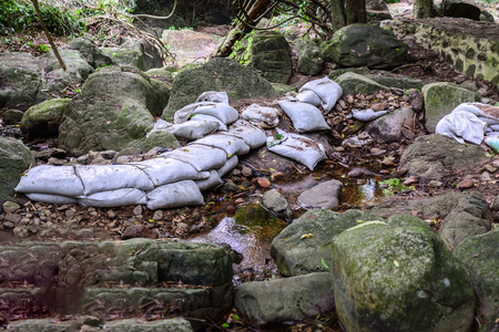 weir: Weir irrigate sand bag at waterfall in forest.