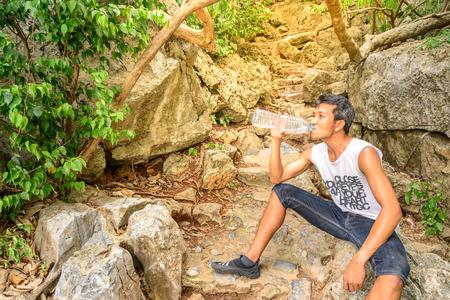 man drinking water: Man hiker drinking water in roasting day.