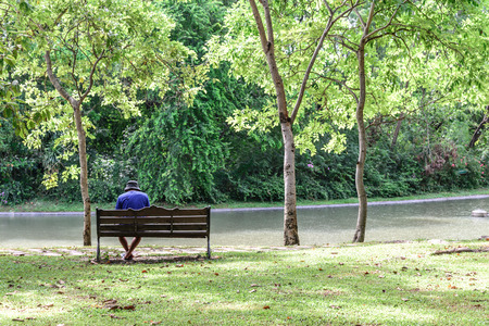 Alone man in blue shirt with hat sitting on wooden bench in park.