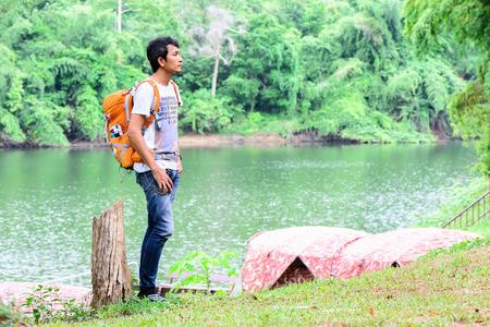 looking at view: Uomo escursionista in jeans blu con zaino arancione guardando vista del fiume.