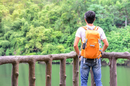 looking at view: Man hiker in blue jean with orange backpack looking view of river. Archivio Fotografico