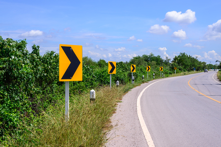 curve: Curve road and right tuning sign with blue sky. Stock Photo
